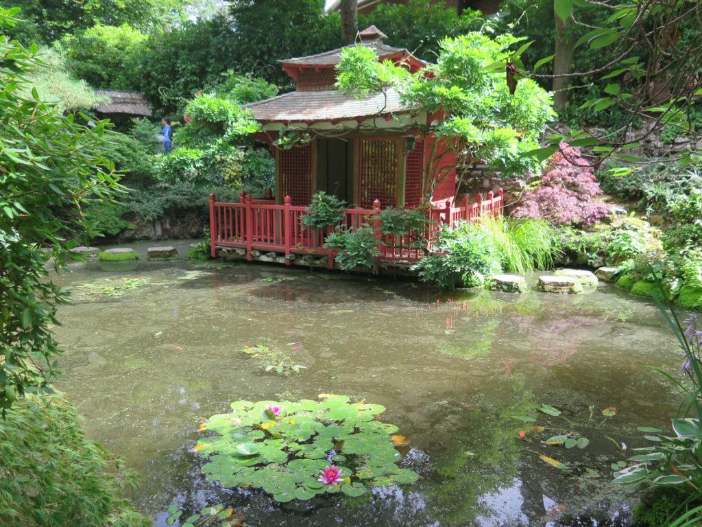 Japanischer Garten mit Häuschen und Seerosen im Vordergrund
