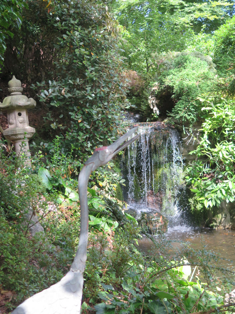 Japanischer Garten mit Skulptur Reiher davor
