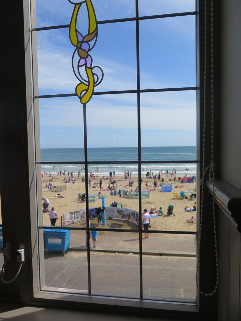 Blick durch ein Fenster auf dem Strand in Bournemouth
