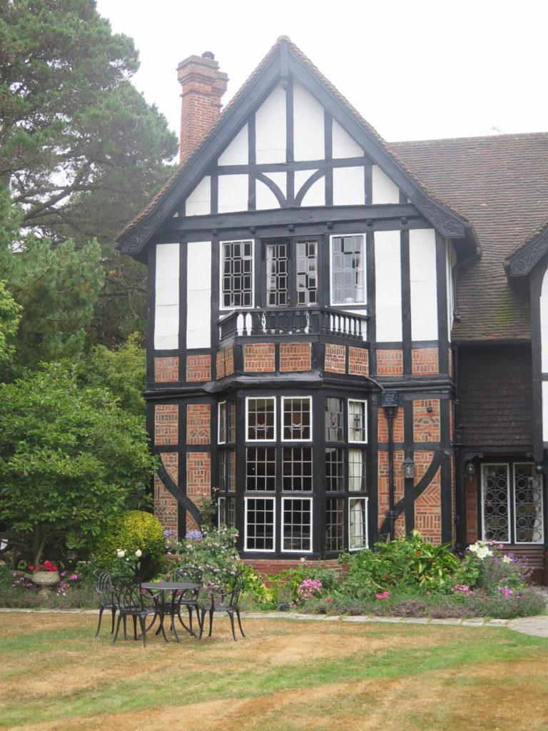 Fachwerk Hotel Tudor House mit Gartenset auf dem Rasen und ein Blumenbeet