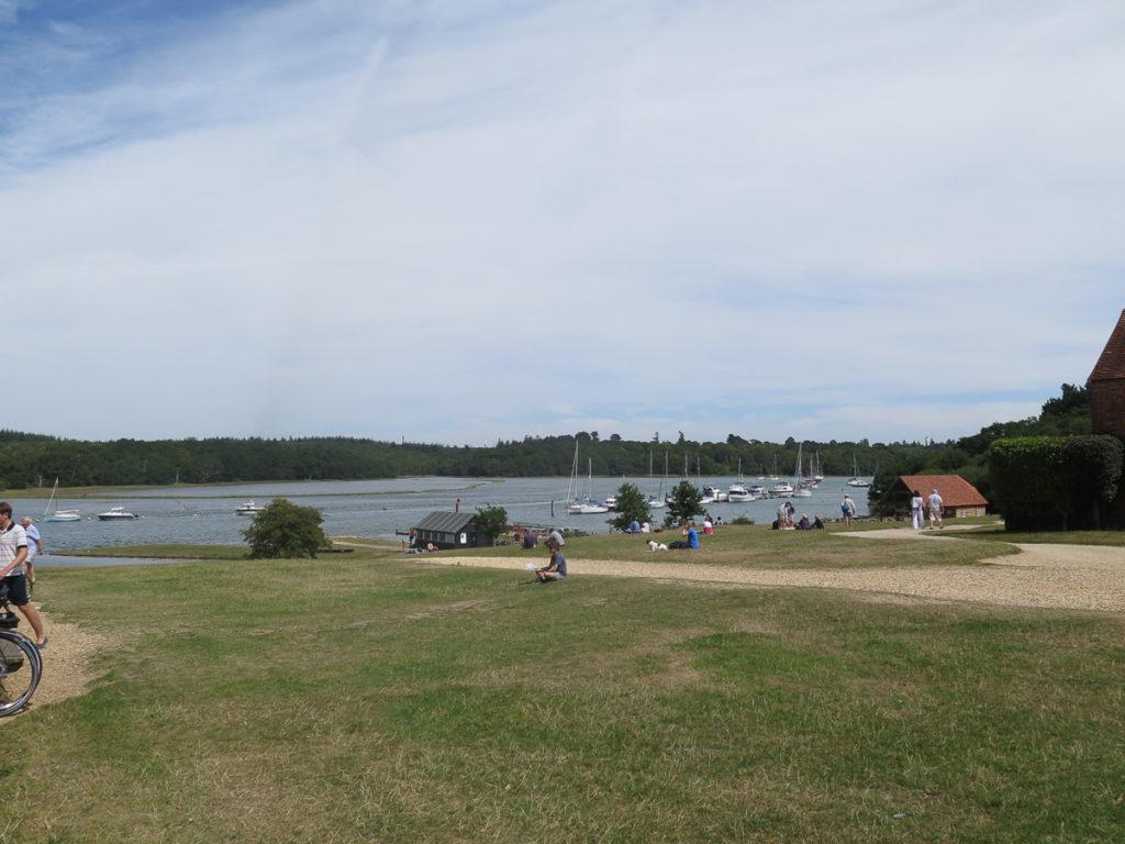 Aussicht auf den Fluss mit Segelboote und Menschen die auf dem Rasen sitzen