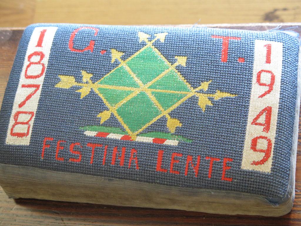 besticktes Kissen mit Wappen drauf und der Text: Festina Lente