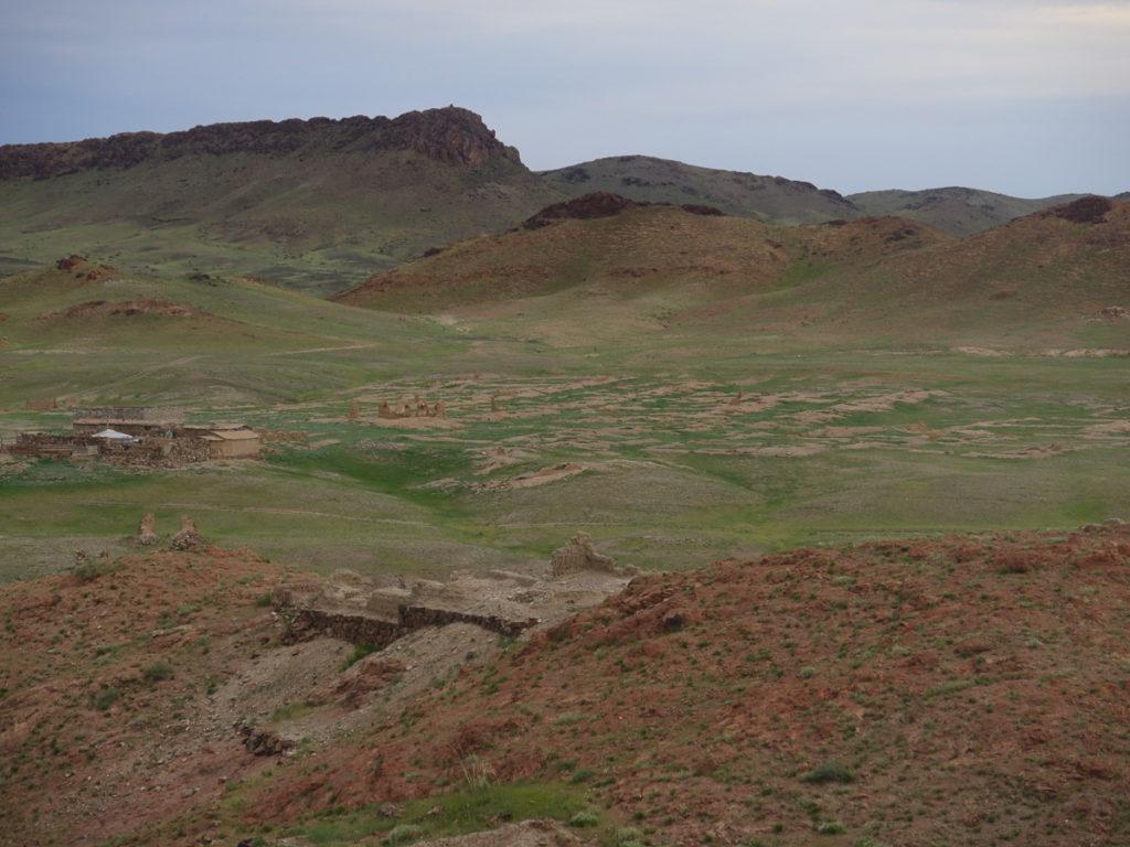 Reste vom Kloster Ongi in der Mongolei. Man sieht hauptsächlich eine grüne Rasenfläche. Im Hintergrund Hügel.