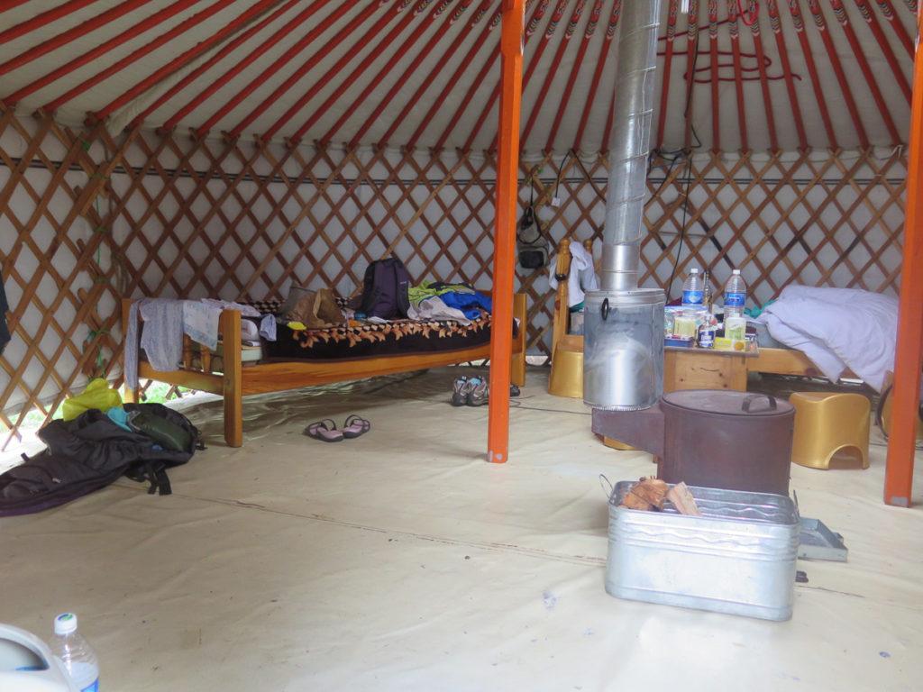 Jurte in der Mongolei innen, ein Ofen mit Rohr nach außen in der Mitte, zwei Betten und viel Gepäck