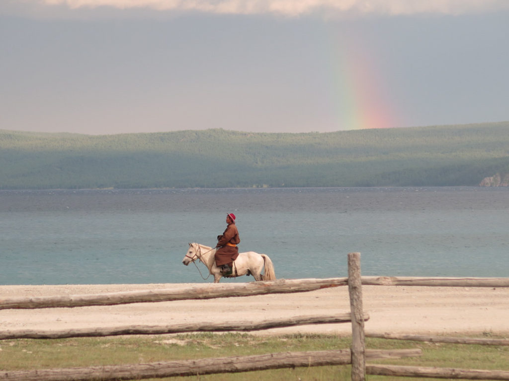 Mann auf weißem Pferd am Chuwsgulsee, im Hintergrund dunkle Wolken und Regenbogen