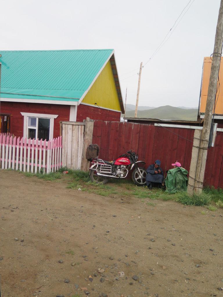Zwei Mongolen angelehnt an Holzzaun mit Regencape und Motorrad daneben