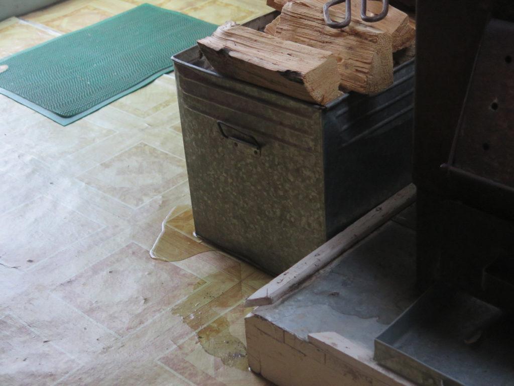 Wasser auf dem Boden von der Jurte neben eine Kiste mit Kaminholz