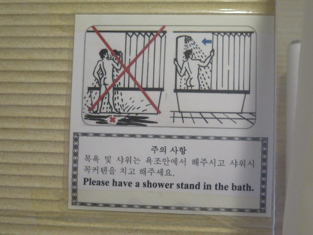 Schild im Bad im Hotel wo gezeigt wird das man sich in der Wanne duschen soll