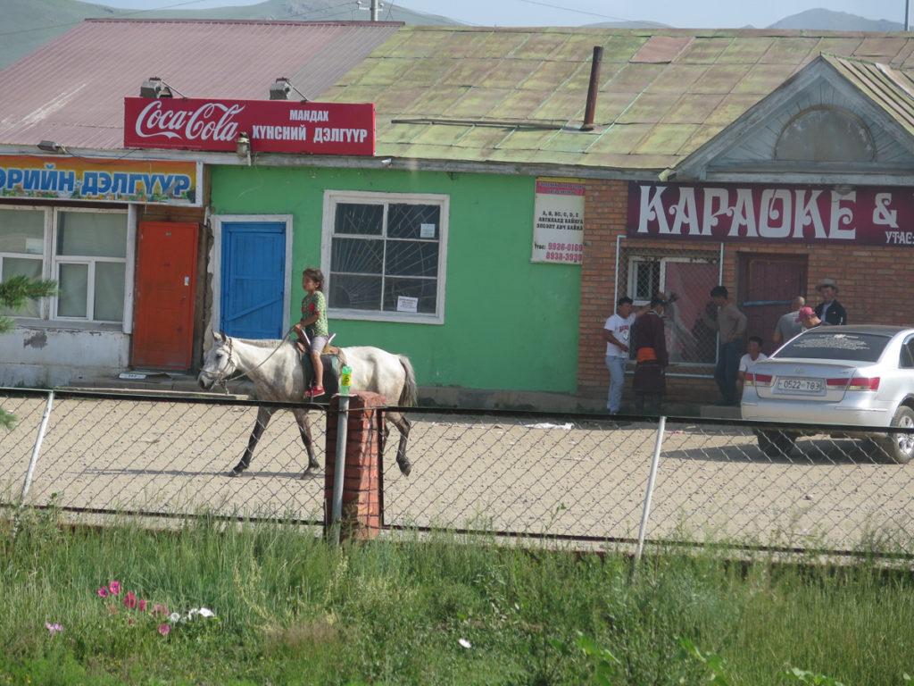 Mädchen auf Pferd vor Karaokebar in der Mongolei