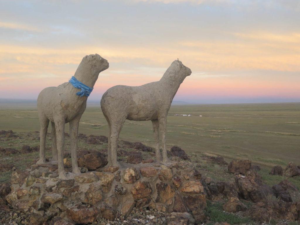 Skulptur von zwei Schafe im Vordergrund, dahinter grüne weite Fläche in der Mongolei, Abendlicht