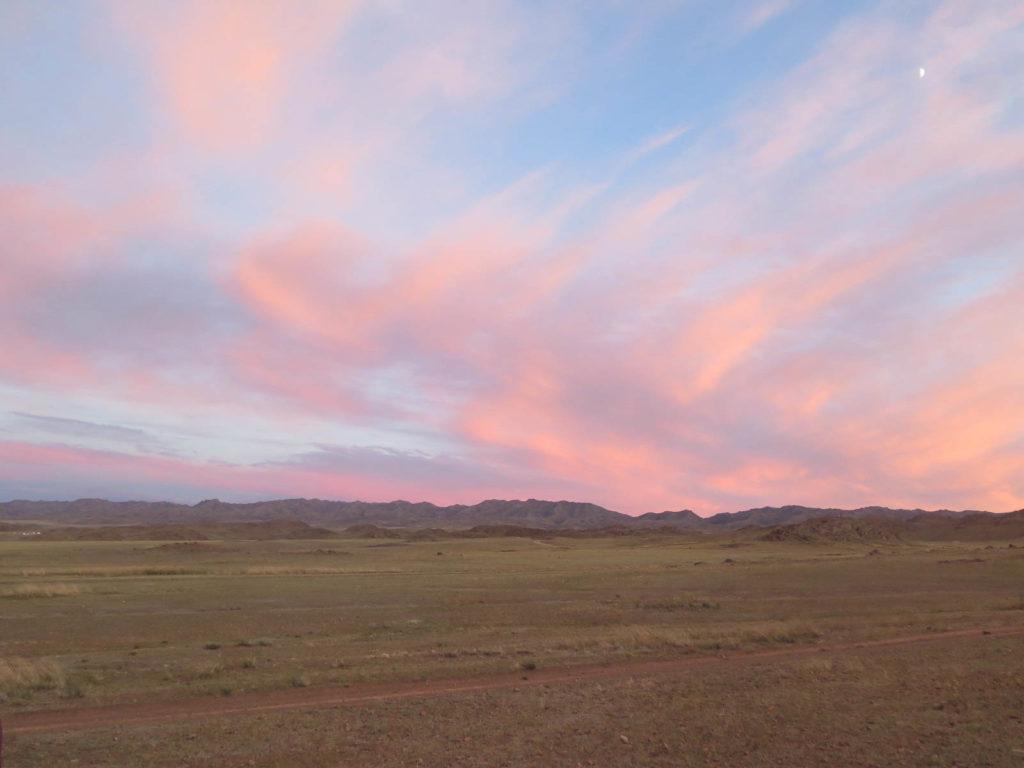 Sonnenuntergang leuchtend rosa in der Mongolei, grüne hügel und viel Gras