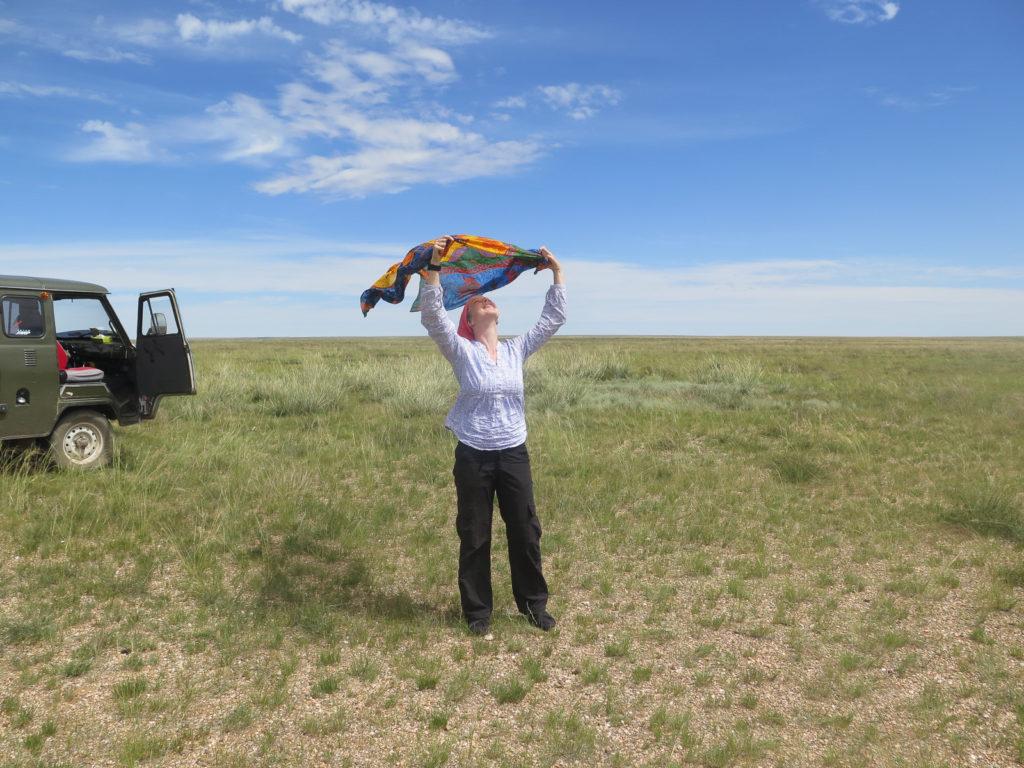 Links ein russischer Bus, blauer Himmel und Gras, Frau spielt mit Tuch im Wind