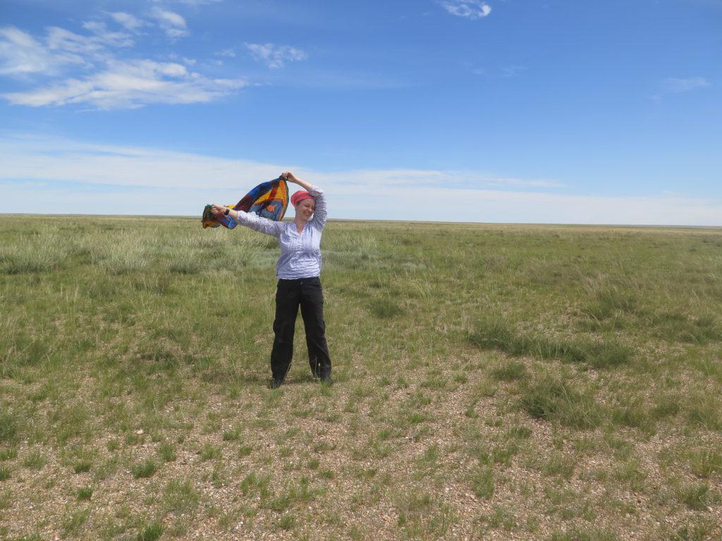 blauer Himmel und Gras, Frau spielt mit Tuch im Wind