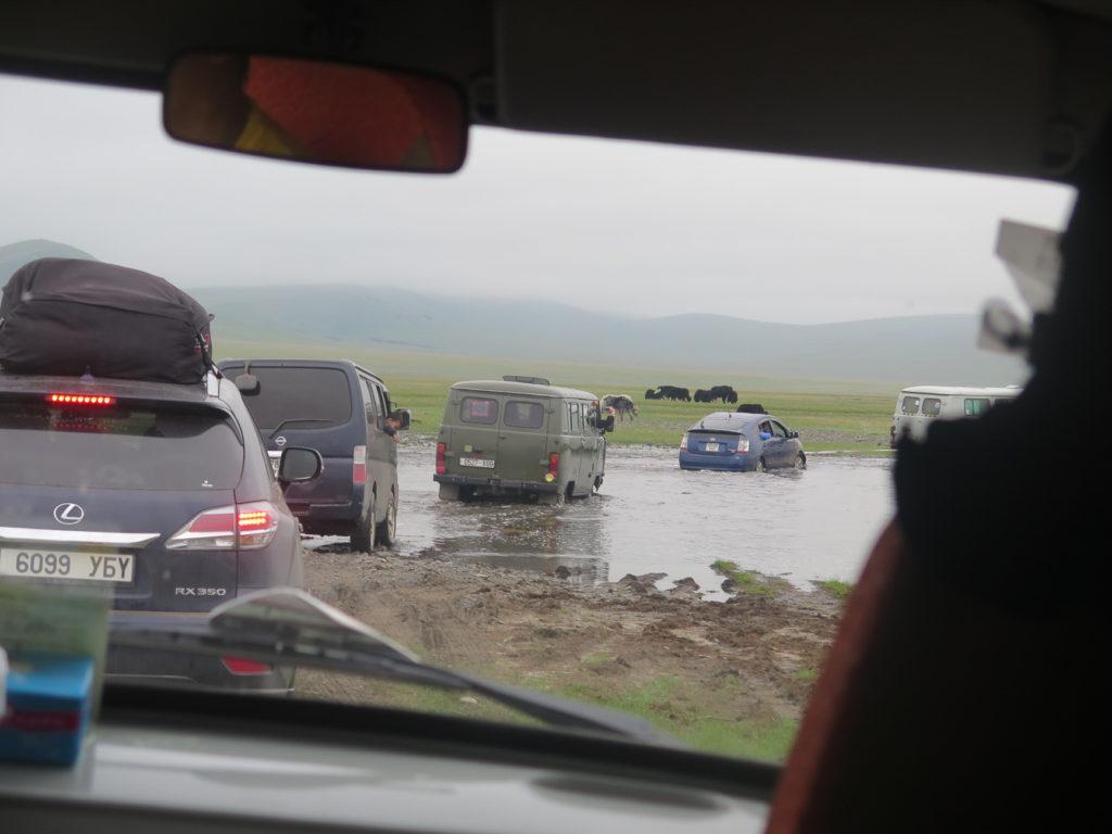 Flussüberquerung, Autos die in Kolonne fahren, im Hintergrund Yaks