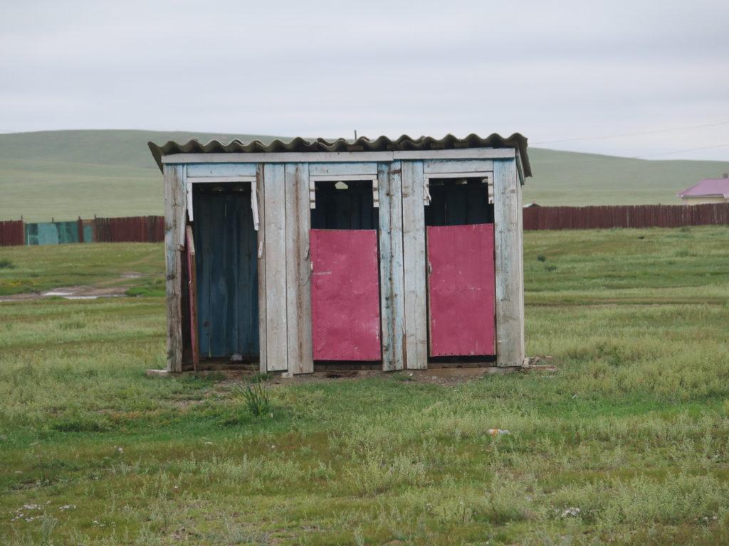 Plumpsklo unterwegs in der Mongolei, alt und dreckig, es fehlt eine Tür