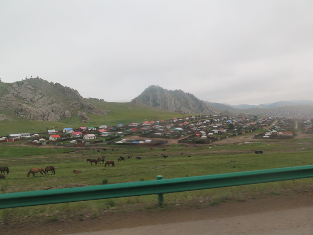 Tsetserleg übersichtsfoto bei der Anfahrt, Pferde im Vordergrund, regnerisches Wetter, tiefhängende Wolken