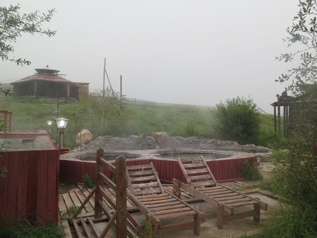 Heisse Quelle Becken im Camp Altan Nutag, im Vordergrund Holzliegen, nebel