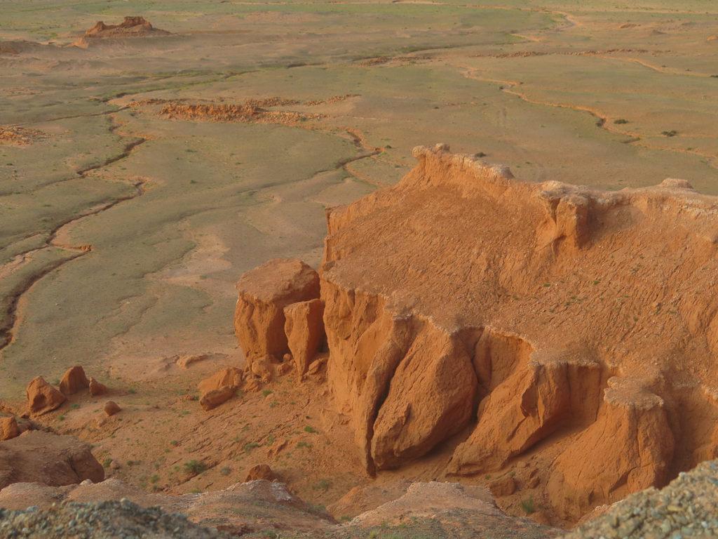 Rote Klippen Bayanzag in der Mongolei, dahinter Steppenlandschaft