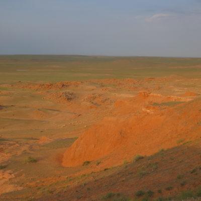 Rote Felsen im Abendrot Bayanzag Mongolei, dahinter Grasfläche Wüste Gobi