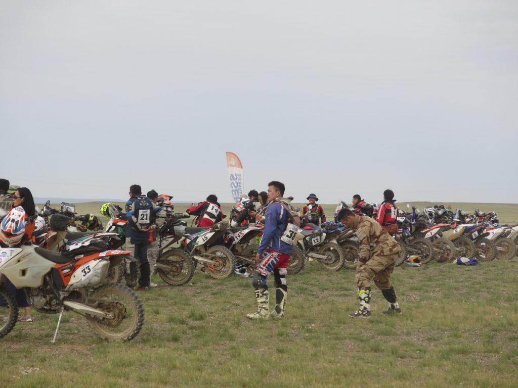 Ralley in der Mongolei, Motorräder aufgereiht für den Start, Fahrer stehen noch daneben