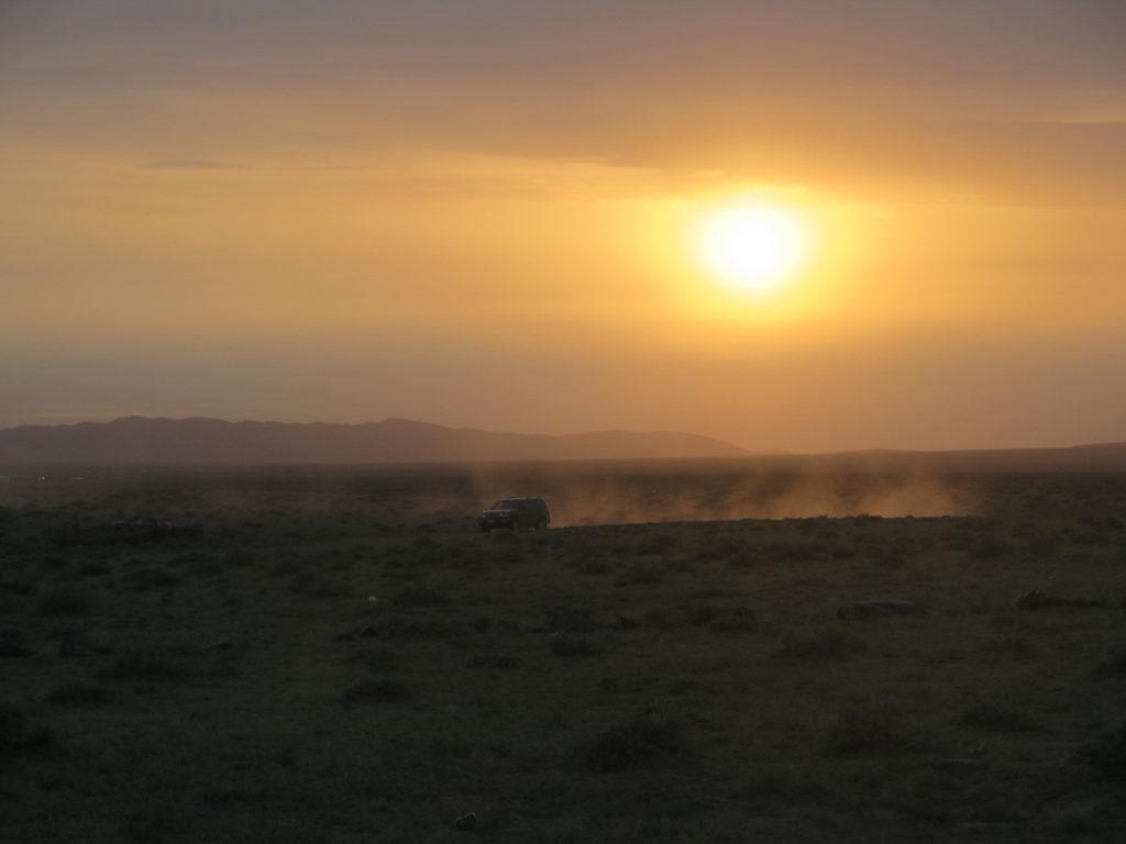 Sonnenuntergang Wüste Gobi im Vordergrund ein Geländewagen der Staub aufwirbelt