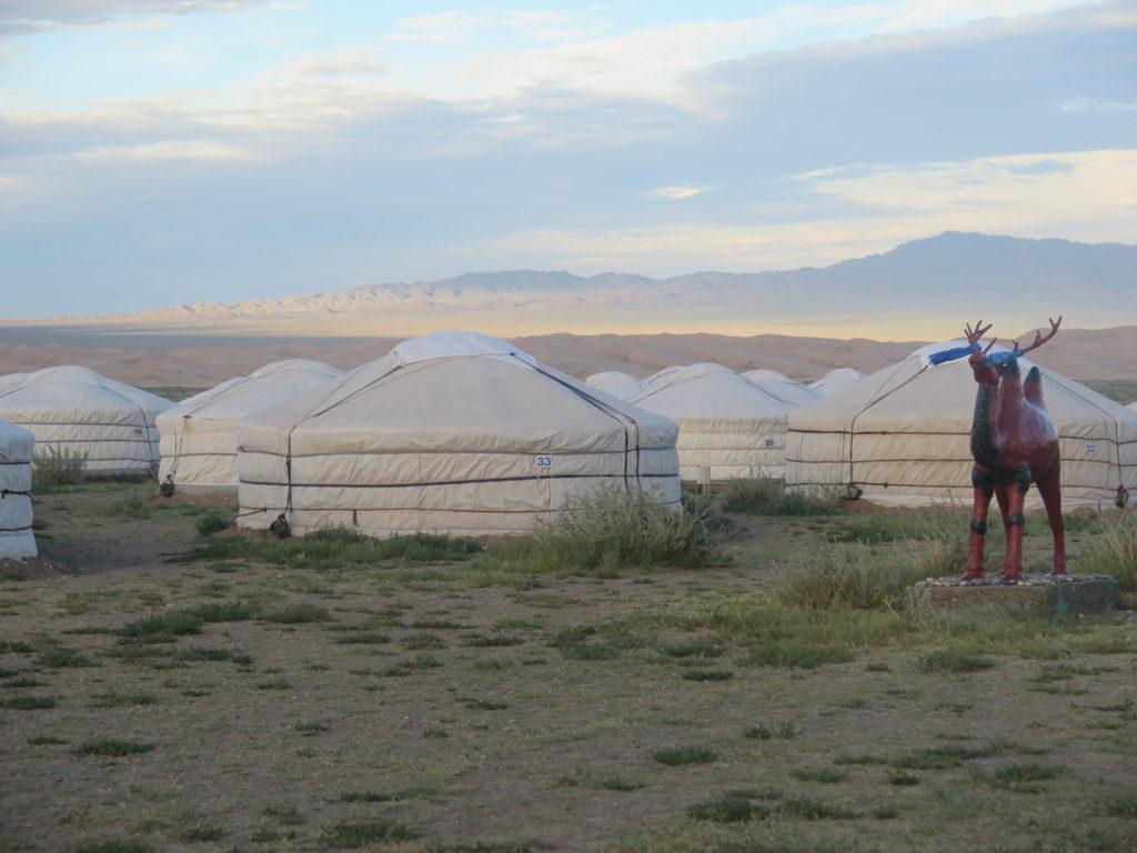 Jurtencamp im Vordergrund, rechts eine Skulptur vom Kamel, im Hintergrund Sanddünen Khongoryn Els