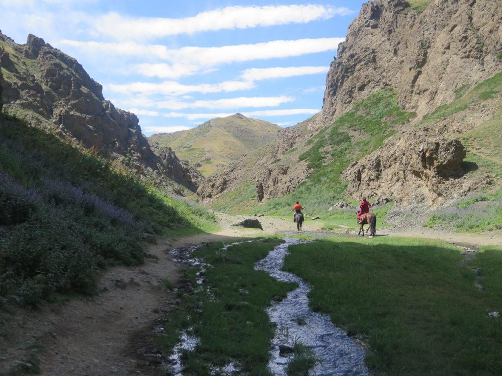 Geierschlucht, kleiner Bach in der Mitte, Felsen, zwei Personen auf zwei Pferde