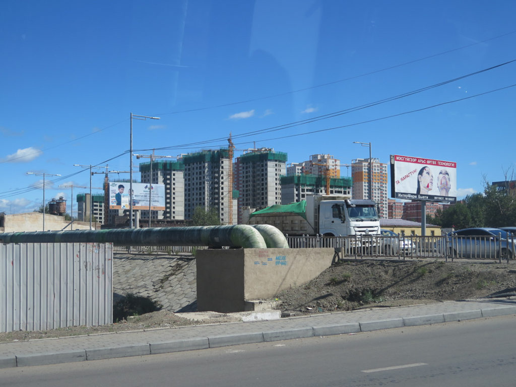 Neubau Hochhäuser in Ulaanbaatar, im Vordergrund große Röhre, Autos und Werbeplakate
