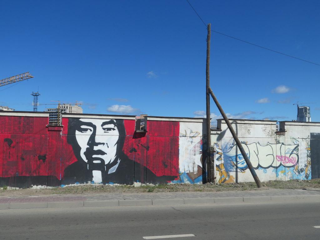 Wandmalerei in Ulaanbaatar, Mann in schwarz/weiss gegen roter Hintergrund