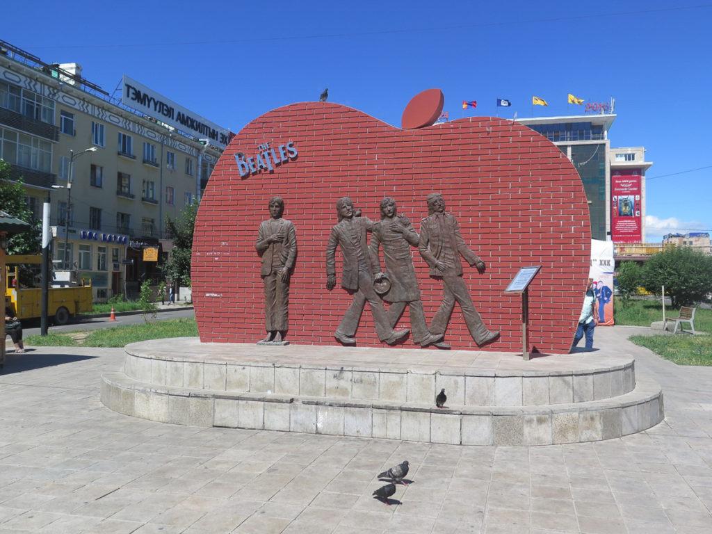 Beatlesmonument in Ulaanbaatar, ein roter Backstein Apfel mit Beatlesfiguren drauf