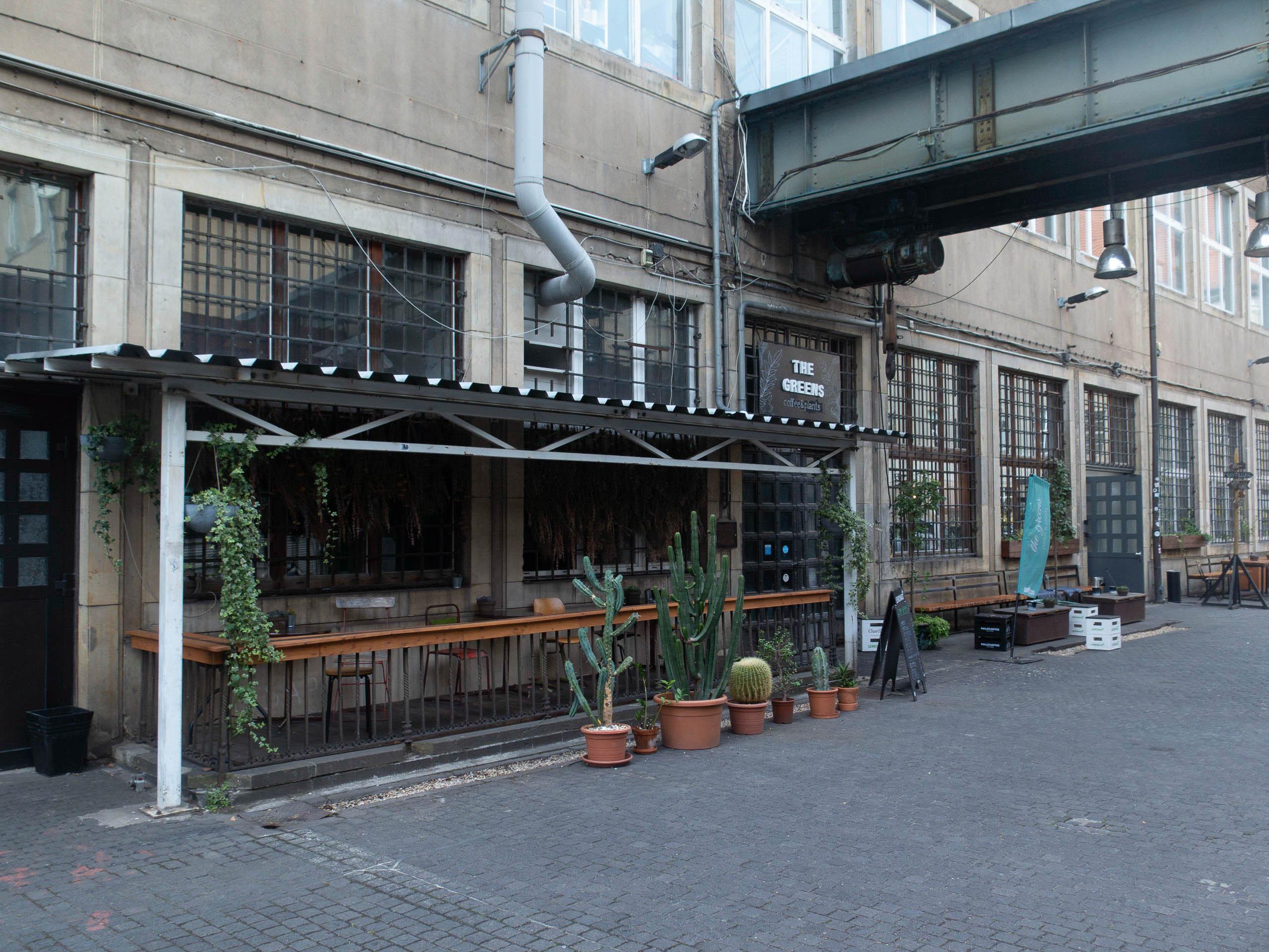 Außenansicht Cafe The Greens, überdachte Terrasse davor mit Stühle, vor der Terasse Pflanzen, industrial