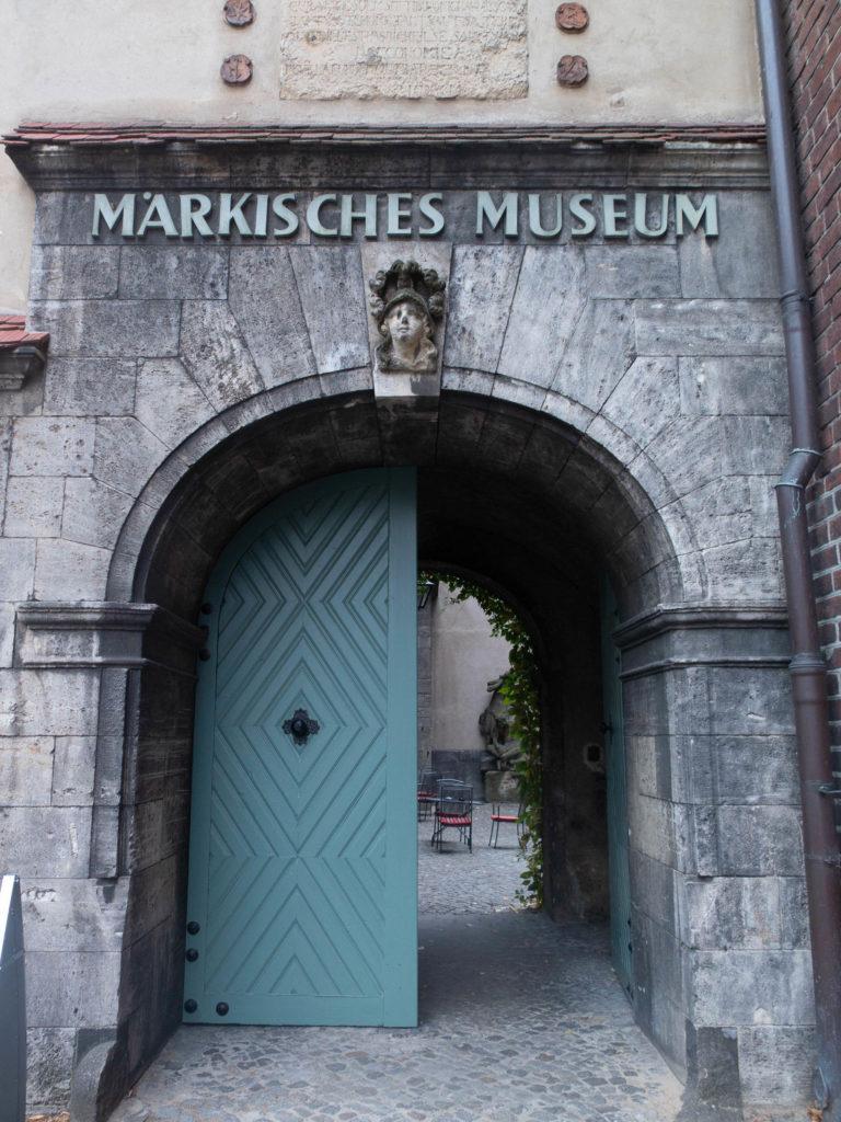 Eingang Märkisches Museum mit grüne Holztür halbgeschlossen, Innenhof mit Stühle und Tisch