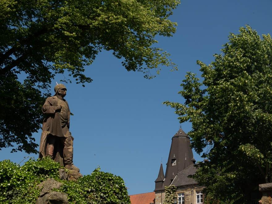 Skulptur Bismarck im Hintergrund Kirchenturm, sonst Bäume und blauer Himmel