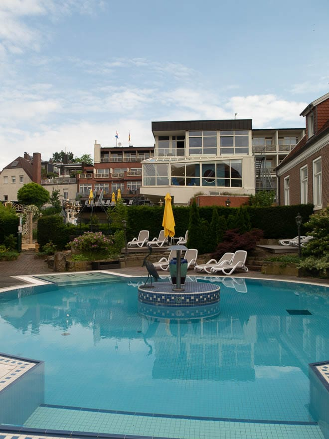 Blick auf Pool und Hinterseite Hotel Grossfeld mit Sonnenliegen und Terrasse
