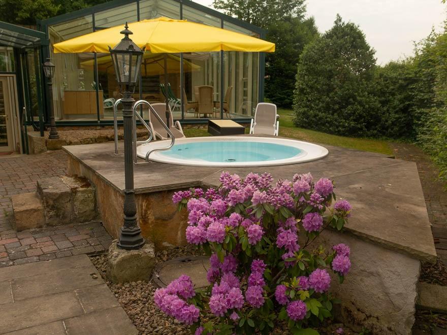 Whirlpool in Hotel Grossfeld mit Rhodondendron vorne und hinten gelber Sonnenschirm