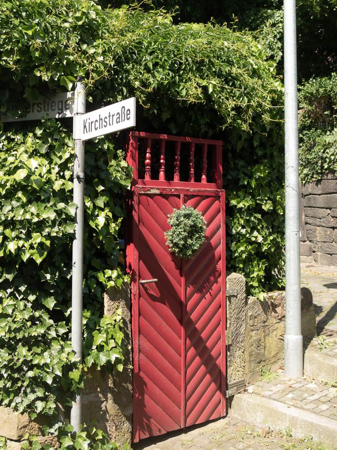 Rotes Gartentor umrahmt von Efeu und Straßenschild wo Kirchstraße drauf ist