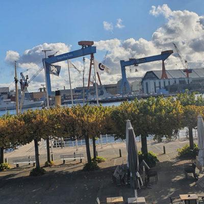 Blick auf der Kieler Förde, vorne Bäume mit Herbstlaub, hinten der Werft, blauer Himmel dramatische weiße Wolken
