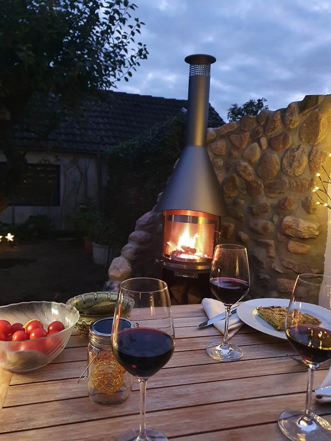 Gartenkamin mit Feuer, im Vordergrund Holzgartentisch mit Weingläser und Essen