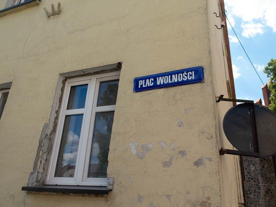 Gelbes Haus mit Schild 'Plac Wolnosci', Fenster