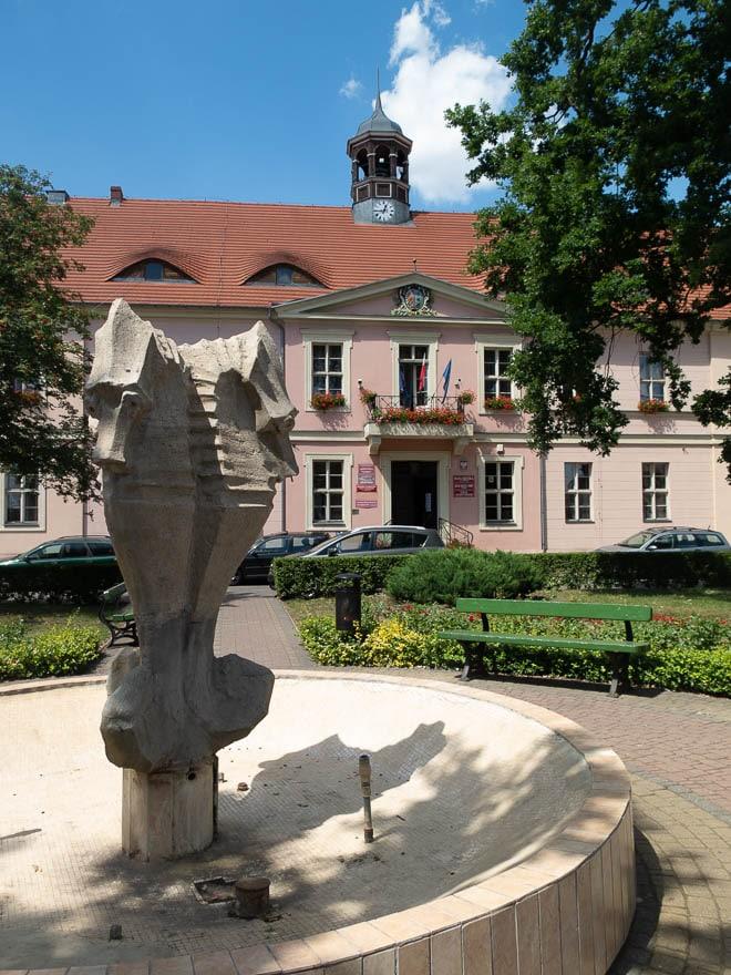 Rathaus Lippehne in rosa mit Brunnen davor