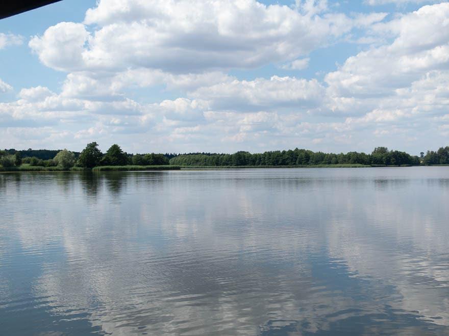 See mit im Hintergrund Bäume, blauer Himmel mit viel weiße Wolken
