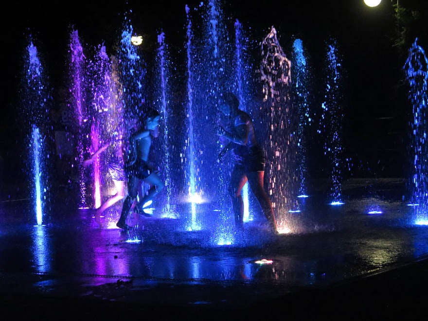 Singende Fontäne Zar Simeon Park Plovdiv am Abend, lila beleuchtet. Menschen rennen durch die Fontäne