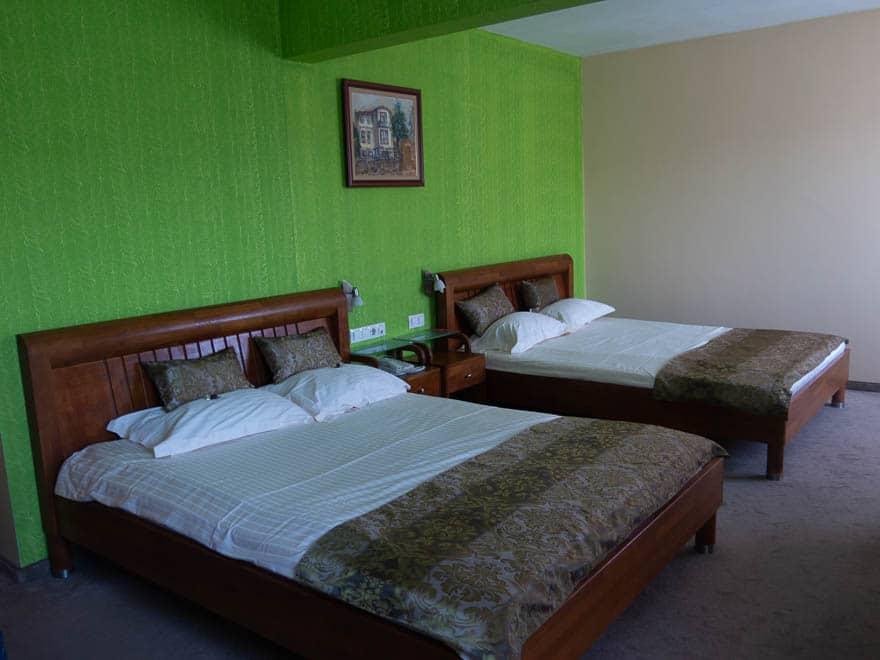 Hotelzimmer in Velingrad, grüne Wand und zwei Doppelbetten aus holz