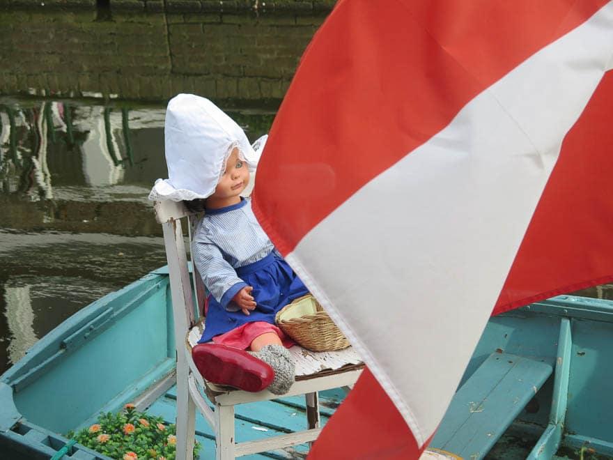 Puppe in niederländische Tracht im Boot mit rot-weiße Fahne