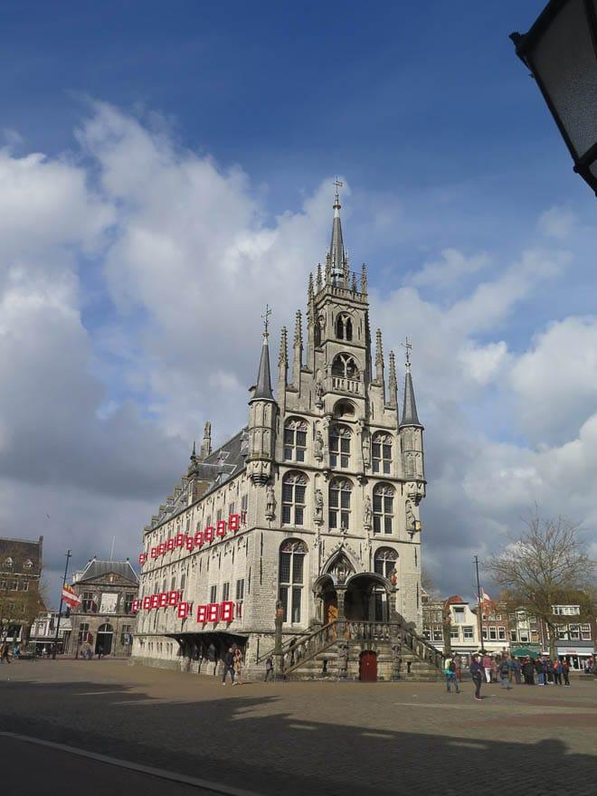Rathaus Gouda, gotisch mit Türmchen und rote Fensterläden, Marktplatz, blauer Himmel mit weiße Wolken