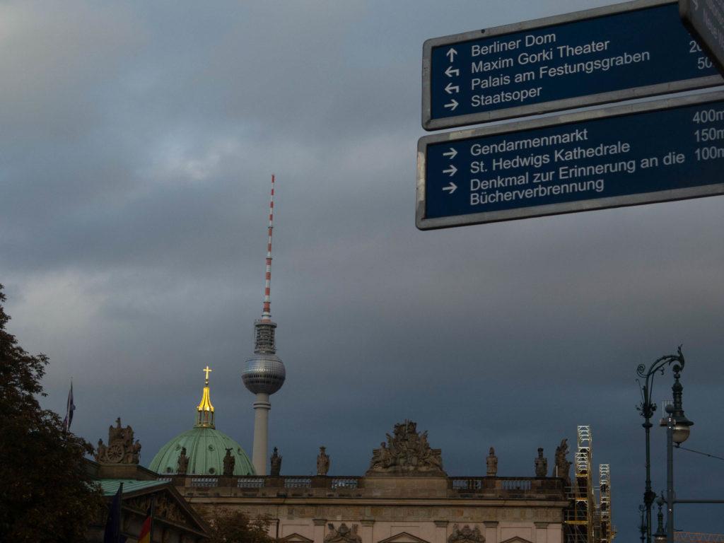 Blick auf der Kuppel vom Berliner Dom und den Fernsehturm, im Vordergrund Wegweiser, dunkelgrauer Himmel