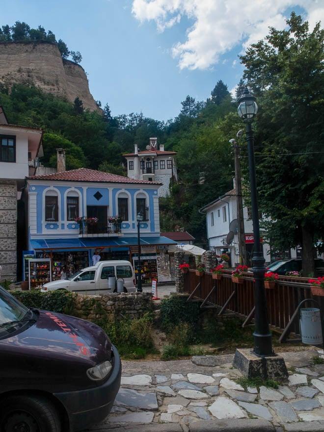 Melnik blaues Haus im Vordergrund, hinten Sandsteinfelsen
