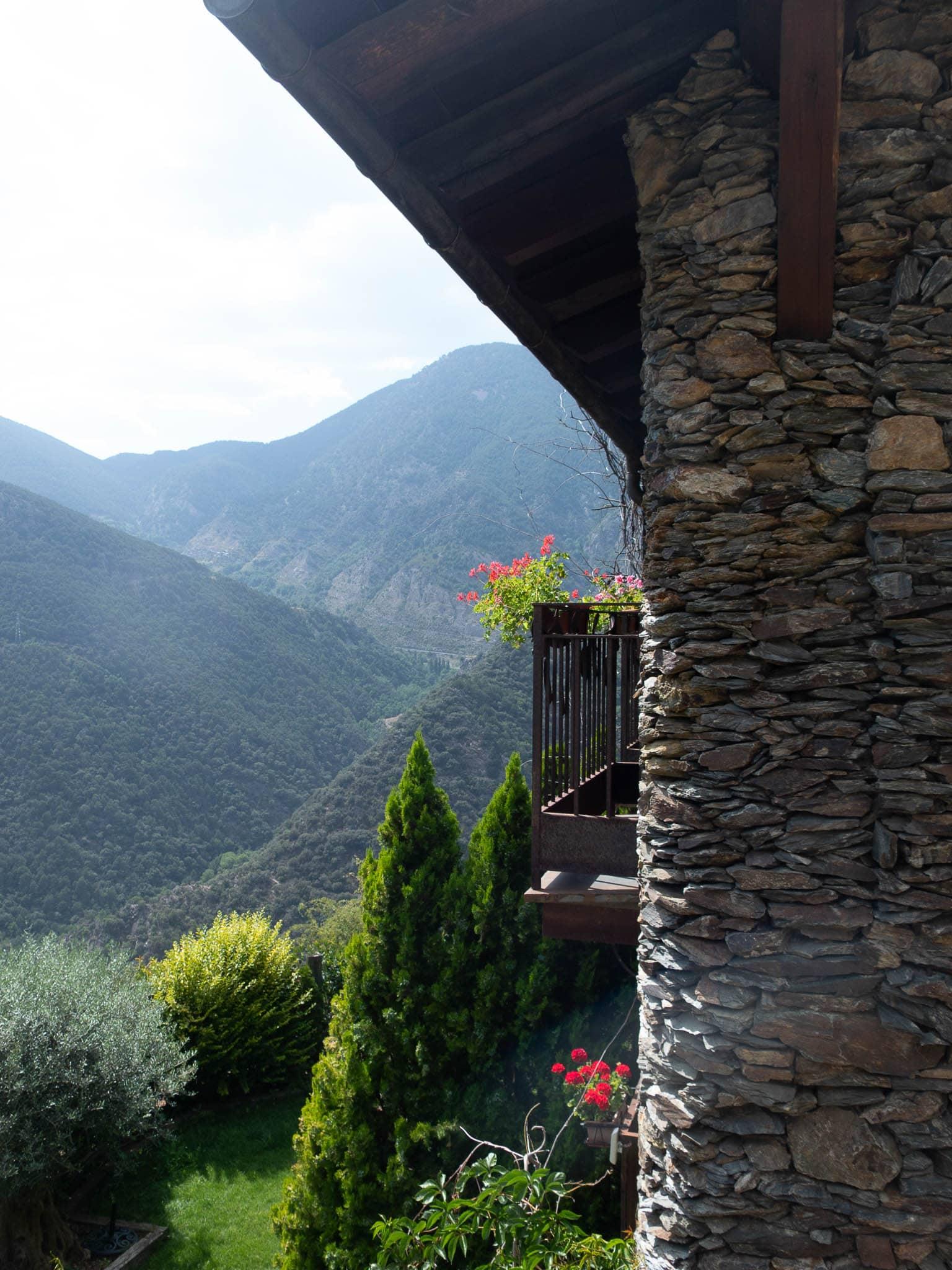 Im Vordergrund Haus mit Balkon und Geranien, im Hintergrund die Pyrenäen