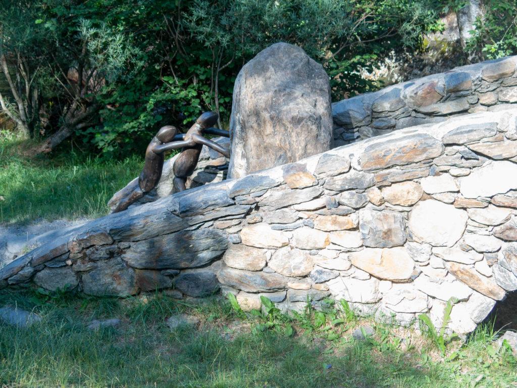 Skulptur auf dem Eisenweg in Andorra, zwei Figuren schieben ein Felsen eine Brücke hoch