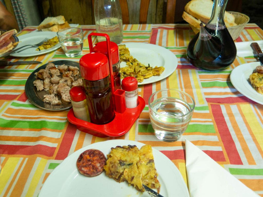 Tisch mit Teller mit Tortilla, Wurst, Wein